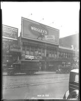 125th Street between Seventh Avenue and Lenox Avenue, New York City, May 28, 1928: Palisades Amusement Park (partial), Wrigley's Double Mint Gum. Also storefronts of Ideal Shoe Shop, Toby's Men's Shop, Christensen School of Music, Orient Photo Plays, Leig