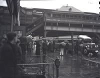 Unidentified New York street scene in rain, showing elevated train station, undated.