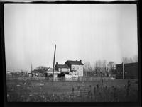 Flatlands: wide view across an unidentified field to houses and other buildings, undated.