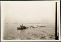 New York City: tugboat 'Dr. George J. Moser,' garbage scows, Ellis Island in distance, 1908.