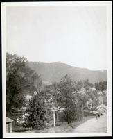 Unidentified view of railway crossing, bridge, and mountains in distance, undated.