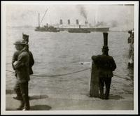 New York City: Men on dock watch as unidentified ocean liner passes, undated.