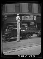 New York City: Mr. Dorie Eddie on stilts, Broadway and Morris Street, advertising the College Cafeteria, undated