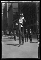 New York City: Mr. Dorie Eddie on stilts, Broadway and Morris Street, advertising clothes, undated
