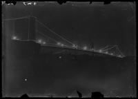 New York City: Brooklyn Bridge, undated. Night view with illuminations.
