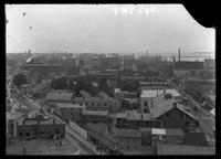 New York City: panorama of Brooklyn, showing signs for Elmer & Bray Harnesses, Smith's Stable, Columbia Steam Dye Works, Wyman & Poller Grocers, and James E. Daley Barber, 1907.