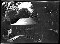Westchester County: [woman and child play in front of unidentified bungalow surrounded by trees, undated.]