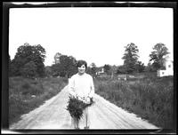 Westchester County: [unidentified woman standing in a country lane holding flowers, undated.]