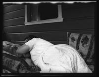 Westchester County: [unidentified woman sleeping against the exterior wall of a wood bungalow, undated.]