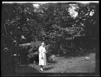 Westchester County: [unidentified woman standing in the yard of a bungalow in the woods, undated.]