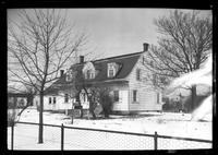 Gravesend / New Utrecht / New Lots / Canarsie: [unidentified Dutch-style house with addition and chain-link fence, in winter, undated.]