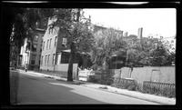 Manhattan / Brooklyn: [unidentified residential side street with backyard trees visible over fences, undated.]