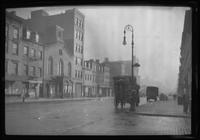 Manhattan / Brooklyn: [misty view of unidentified commercial intersection, undated. Heavily-loaded horse cart visible.]