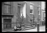 Manhattan / Brooklyn: [front door and stoop of unidentified brick townhouse, with three small boys sitting at the bottom of the railing, undated.]