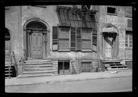 Manhattan / Brooklyn: [entryways to two unidentified townhouses, in heavy disrepair, undated.]