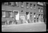 Manhattan / Brooklyn: [front doors and stoops of three unidentified brick townhouses, undated. Middle House has 'for sale' sign.]