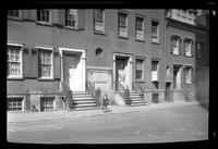 Manhattan / Brooklyn: [front doors and stoops of three unidentified brick townhouses, undated. Middle House has 'for sale' sign. Small boy on tricycle in frame center. Slightly out of focus.]