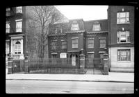 Manhattan / Brooklyn: [unidentified house with mansard roof, high fence and deep front garden, sandwiched between larger buildings, undated. 'For sale' sign displayed.]
