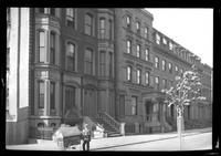 [Brooklyn: unidentified townhouses, undated. Man pushing laundry cart in foreground.]
