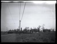 Long Island City: [view down an unidentified dirt road with trolley tracks to a small cluster of buildings,  including a cemetery, undated.]