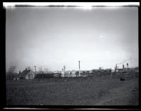 Long Island City: [Lauruich-Leverich Burial Ground (i.e. Lawrence Cemetery), seen from the rear, 1923. Steaming smokestack and water tower in the distance.]