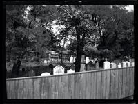 Long Island City: [unidentified cemetery with trees, surrounded by wooden fence, undated.]