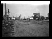 Newtown: [unidentified bare lots with buildings, church, and billboards in distance, undated.]