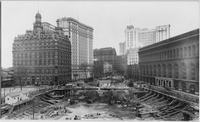 Manhattan: Bowling Green, with the excavations for the U.S. Custom House in the foreground, undated [ca. 1904]. New York Produce Exchange, the Washington Building, and the Mail Express Building visible.