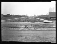 Banker Street looking east from Meserole Avenue, Hilton Estate, Long Island City, Queens, undated. Trolley tracks, vacant lot, gas tanks. Photographed for Joseph P. Day.