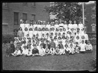 Group portrait of children posed between brick buildings, Fr. Leiser, June 7, 1920. [Possibly the Roman Catholic Orphan Asylum, Kingsbridge, Bronx.]