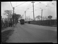 View north on Astoria (Road? Boulevard?) with automobiles and trolley, and sign 'To North Beach,' Queens, undated (ca. 1920).