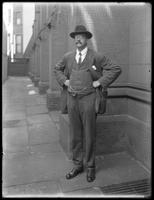 Full-length portrait of Charles S. Midler beside a large stone building (possibly a church?), August 18, 1911. Slightly blurred.