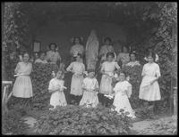 Graduating class of girls from the Roman Catholic Orphan Asylum posed before the grotto with their diplomas, 1912.