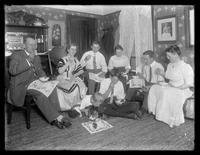 James Welty, Walter Welty, Belle Hassler Welty, Ethel Gray Magaw Hassler, William Gray Hassler, Reddy the cat, and unidentified others seated in an unidentified sitting room eating cake and ice cream, undated (ca. 1913).