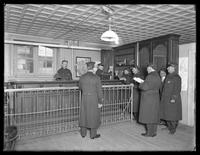 Interior of unidentified police station, showing officers and front desk, undated (ca. 1913-1914).