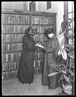 Miss Baldwin of 26 Brevoort Place, and unidentified friend, in the DeKalb branch of the Brooklyn Public Library, Brooklyn, looking up gardening books, November 16, 1914.