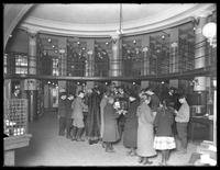 Patrons at the reference desk of the Williamsburgh branch of the Brooklyn Public Library, November 16, 1914. Stacks visible.