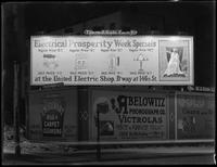 Night shot of billboards at 183rd Street and St. Nicholas Avenue, New York City, November 23, 1915. Photographed for the United Electric Light & Power Company. United Electric shop billboard features Hassler photographs.