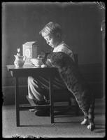 William Gray Hassler seated at a small table eating Quaker puffed rice cereal, with Reddy the cat, undated (ca. 1912).