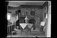 Crag Inch Lodge, Pollepel Island : interior view of the residence : living room, including fireplace which reads 'Jehovah is my strength and shield'. New York, undated.