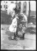 William Gray Hassler with fishing tackle, showing his catch to two unidentified girls (Dorothy and Daisy Sprore?), undated (ca. 1911-1913).