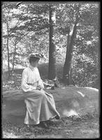Ethel Magaw Hassler posed seated on a boulder in unidentified woods, undated (ca. 1911-1913).
