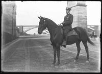 Mounted police officer Fitzgerald on the Speedway under High Bridge, undated (ca. 1911).