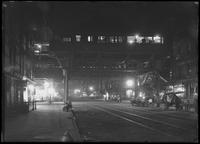 Night view of elevated subway station and unidentified street on the Lower East Side, New York City, undated (ca. June 1917). Vendors' carts stowed for the night.