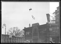 Dare Devil Kid Scheyer on a stunt bike flying above Columbus Circle, New York City, November 27, 1918.