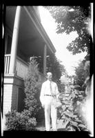 Fritz E. Bjorkman standing in front of a house, undated (ca. 1940-1945).