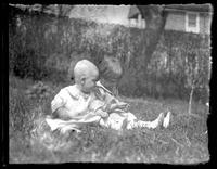 Infant William Bjorkman and toddler Virginia Bjorkman playing in the grass in a garden, undated (ca. 1925-1930).