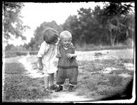 Infant William Bjorkman and toddler Virginia Bjorkman standing in a back garden with woods behind, undated (ca. 1925-1930).
