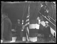 Miss Rita Jolivet, survivor of the 'Lusitania,' raising an American flag over the German U-boat UC-5 during a Liberty Day parade, New York City, October 25, 1917.