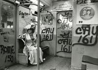 Editta Sherman in costume on graffiti-covered subway car.